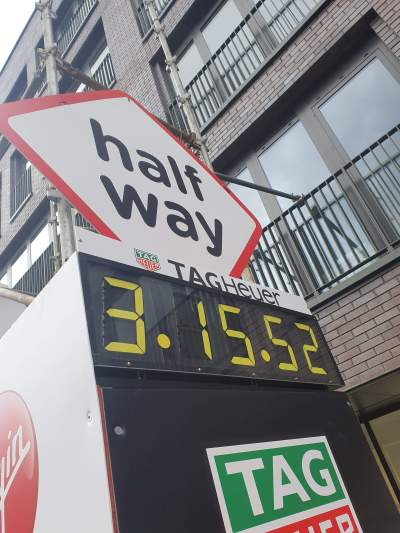 A large diagonal sign saying half way above a clock showing 3 hours 15 minutes have passed