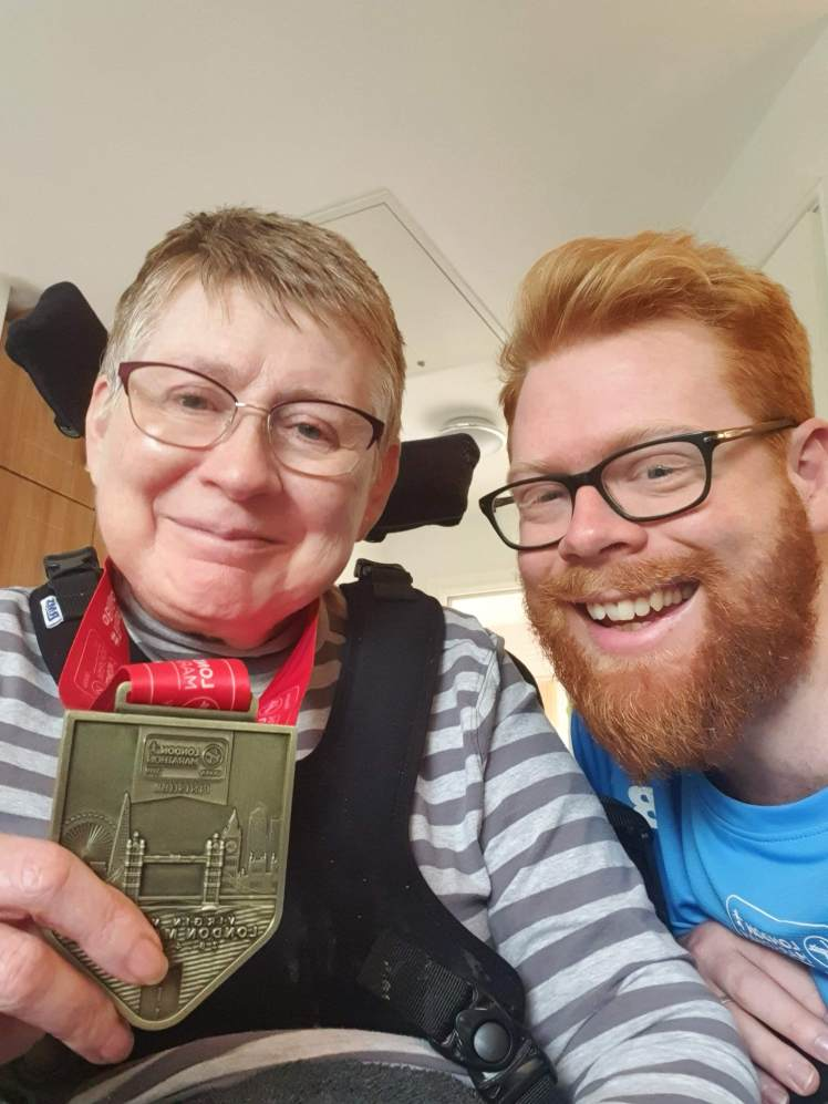 Me and mum both smiling - she is holding the medal I got when I crossed the finish line.